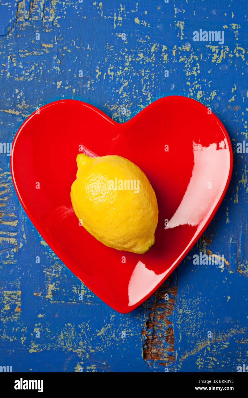 Limón sobre la placa en forma de corazón rojo Imagen De Stock