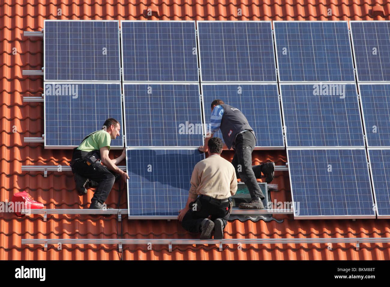 Los obreros la instalación de paneles solares en el techo Imagen De Stock
