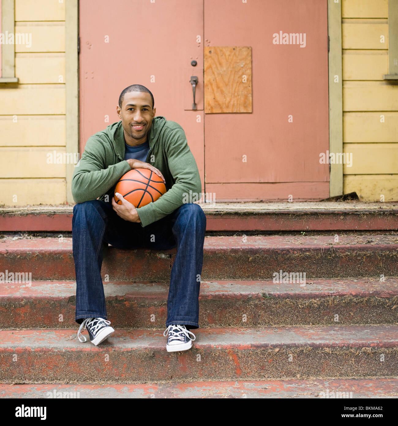 Hombre afroamericano sentado en pasos con el baloncesto Foto de stock