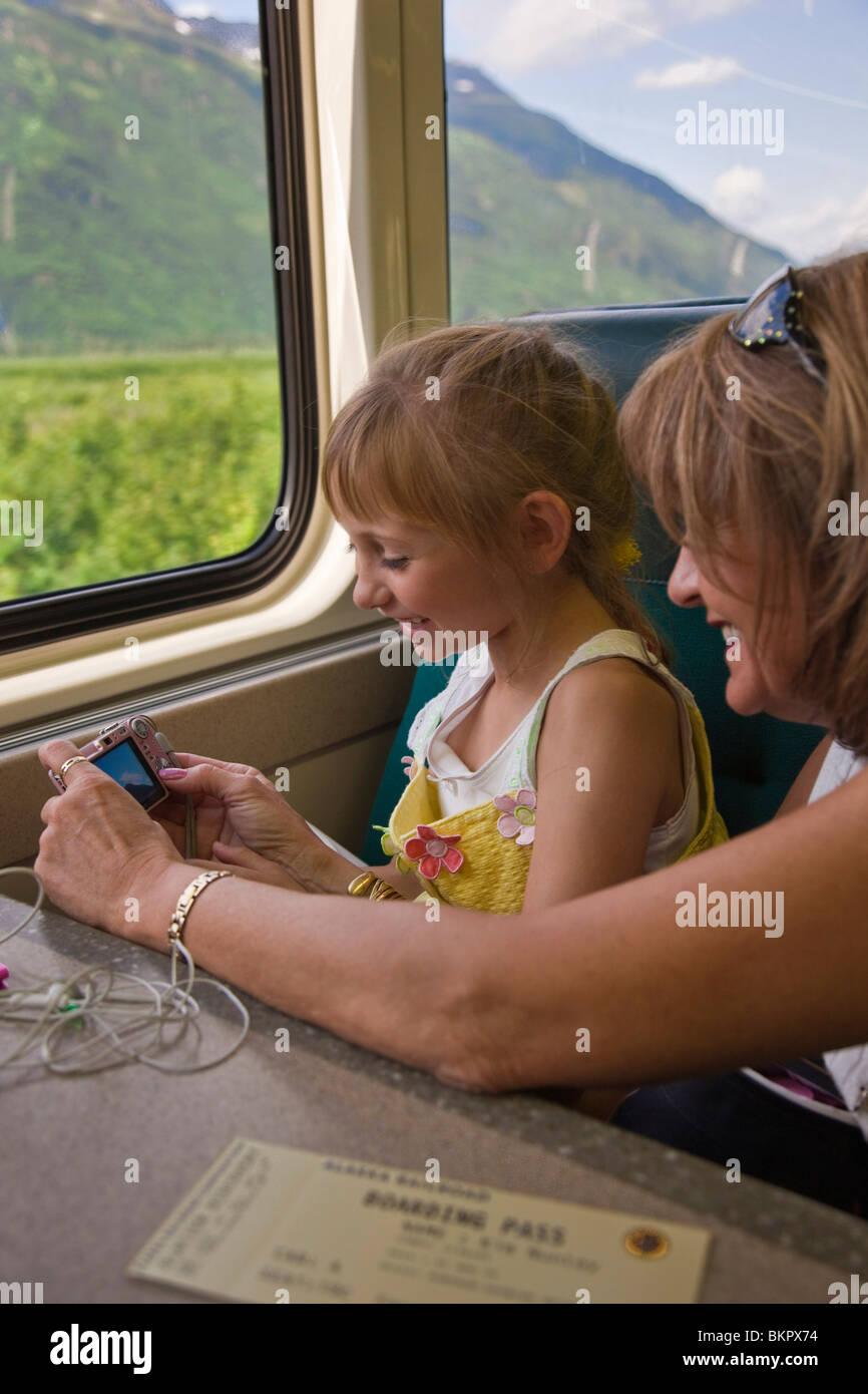 Madre e hija revise las fotografías de una cámara digital mientras viajaba en un tren hasta el glaciar Spencer en Foto de stock