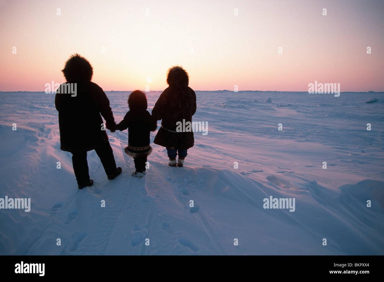 Familia Esquimal Inupiat ver la nieve cubrió la tundra ártica Barrow, Alaska Sunset invierno Imagen De Stock