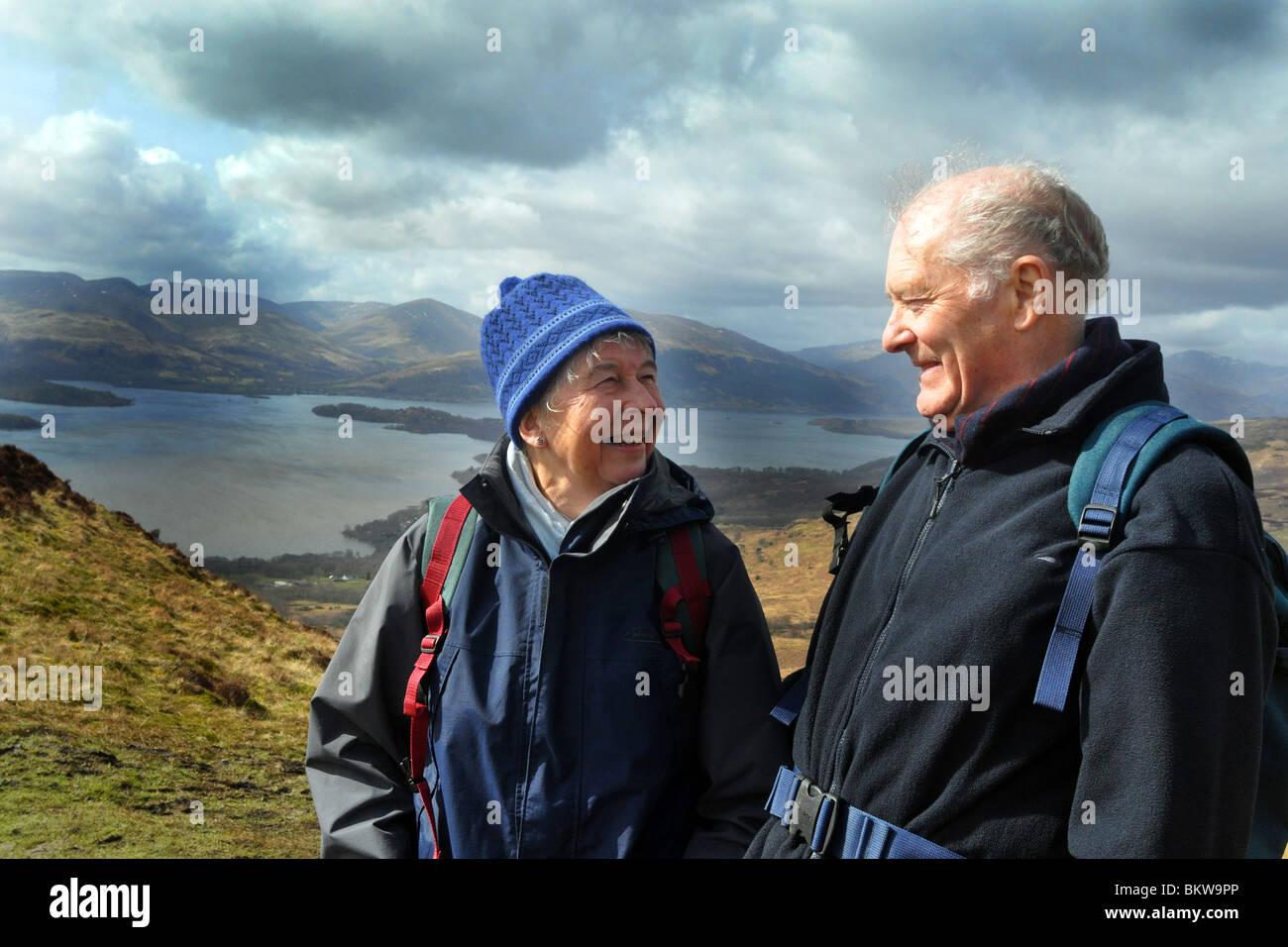 Personas mayores activas practicar el senderismo en el Parque Nacional de Trossachs, Escocia Foto de stock