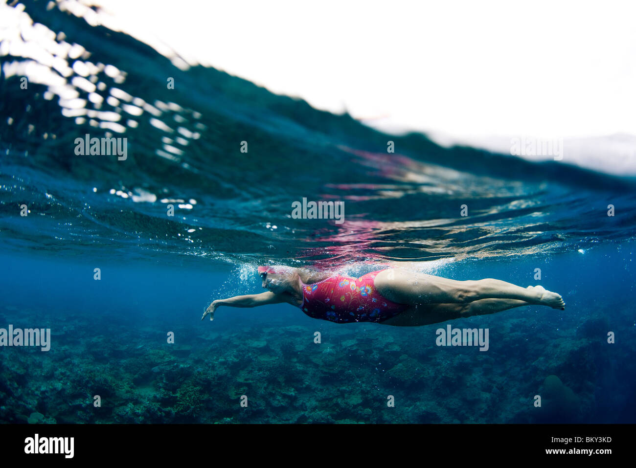Vista submarina de un nadador disfrutando de un relajante baño en las aguas tropicales de la Isla de Mana, Imagen De Stock
