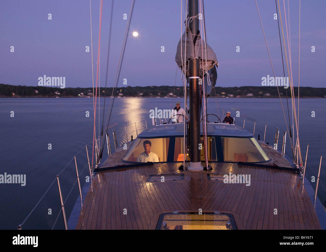 Una tripulación navega en un yate de carreras a casa al anochecer, utilizando instrumentos de alta tecnología. Imagen De Stock