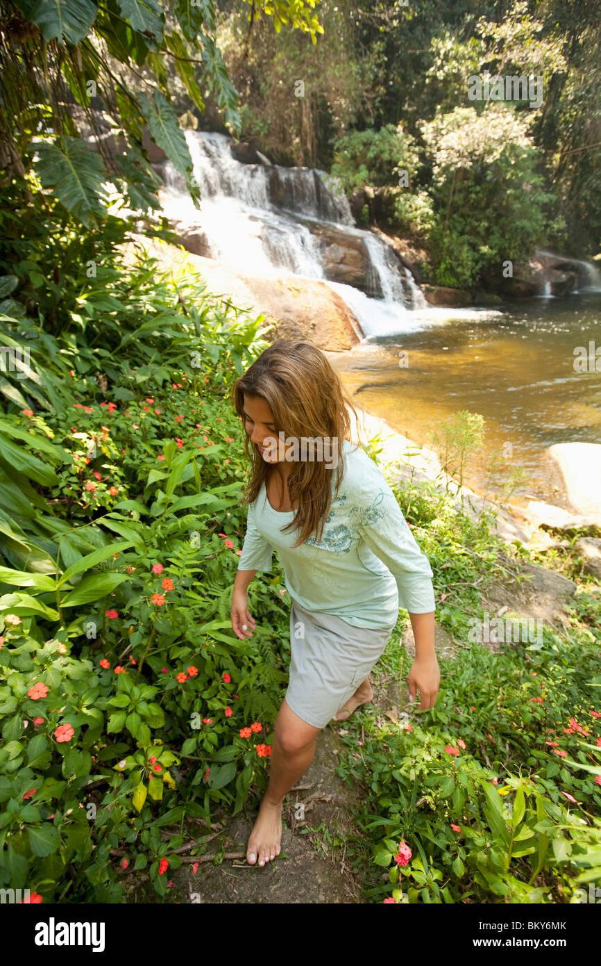 Una mujer caminatas por un sendero tropical junto a una cascada en el Brasil. Foto de stock