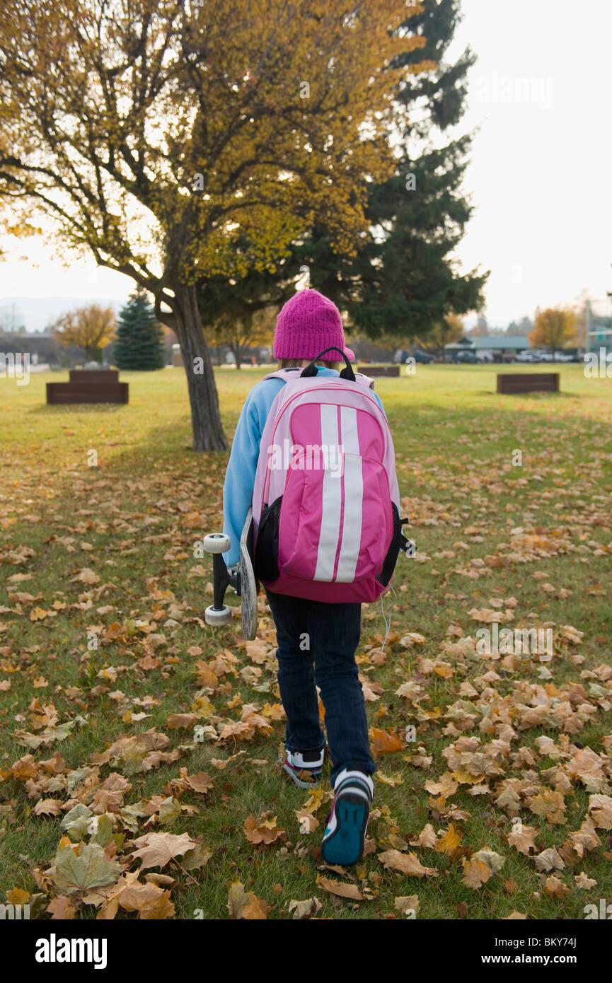 Una chica joven llevando su monopatín, camina a casa desde la escuela en un día de otoño. Foto de stock