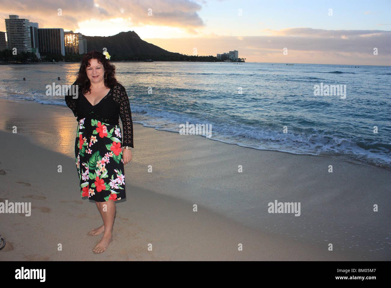 A cuarenta algo señora de pie en la playa de Waikiki, en HAWAII AL AMANECER CON CABEZA DE DIAMANTE EN SEGUNDO Imagen De Stock