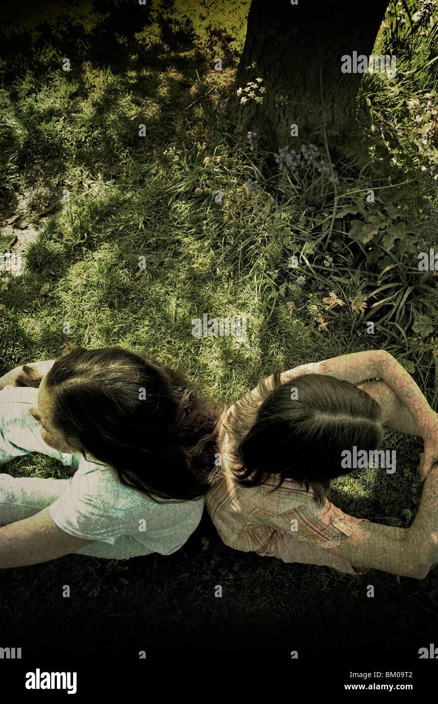Dos jóvenes sentados espalda con espalda bajo un árbol Imagen De Stock