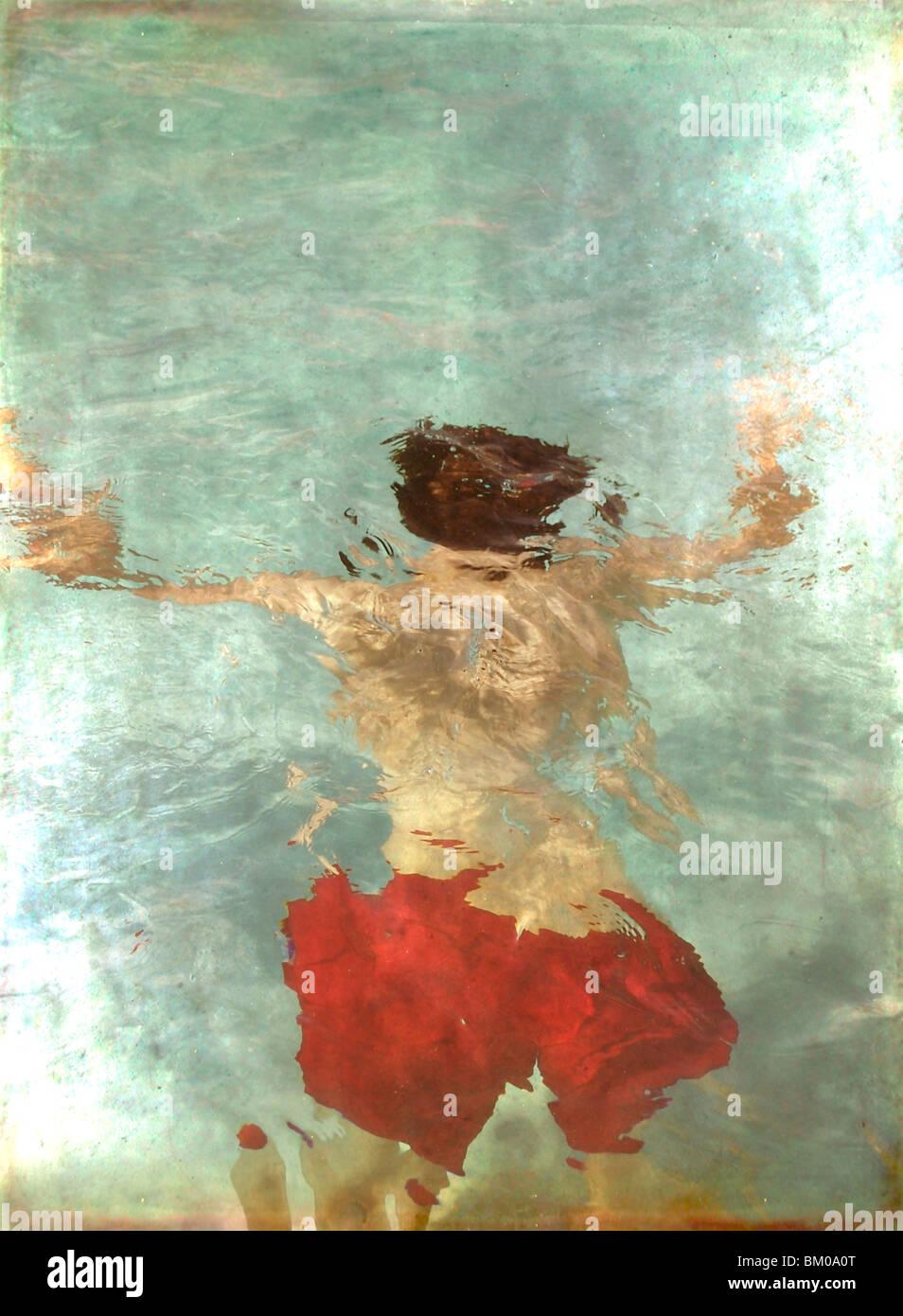 Un adolescente flotando boca abajo en una piscina, vistiendo calzones rojos Imagen De Stock