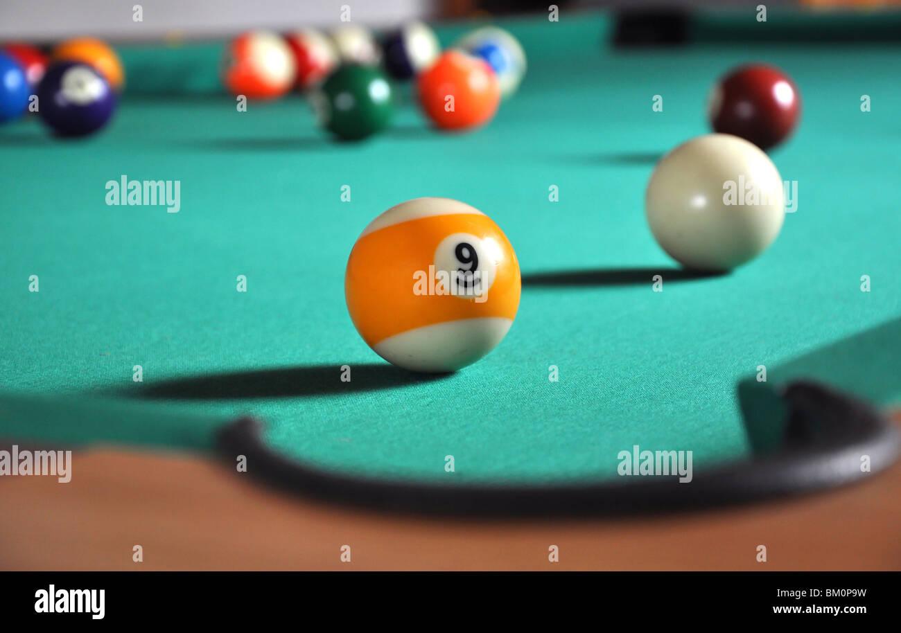 Bola de billar cerca del agujero, un montón de bolas en borroso fondo Imagen De Stock