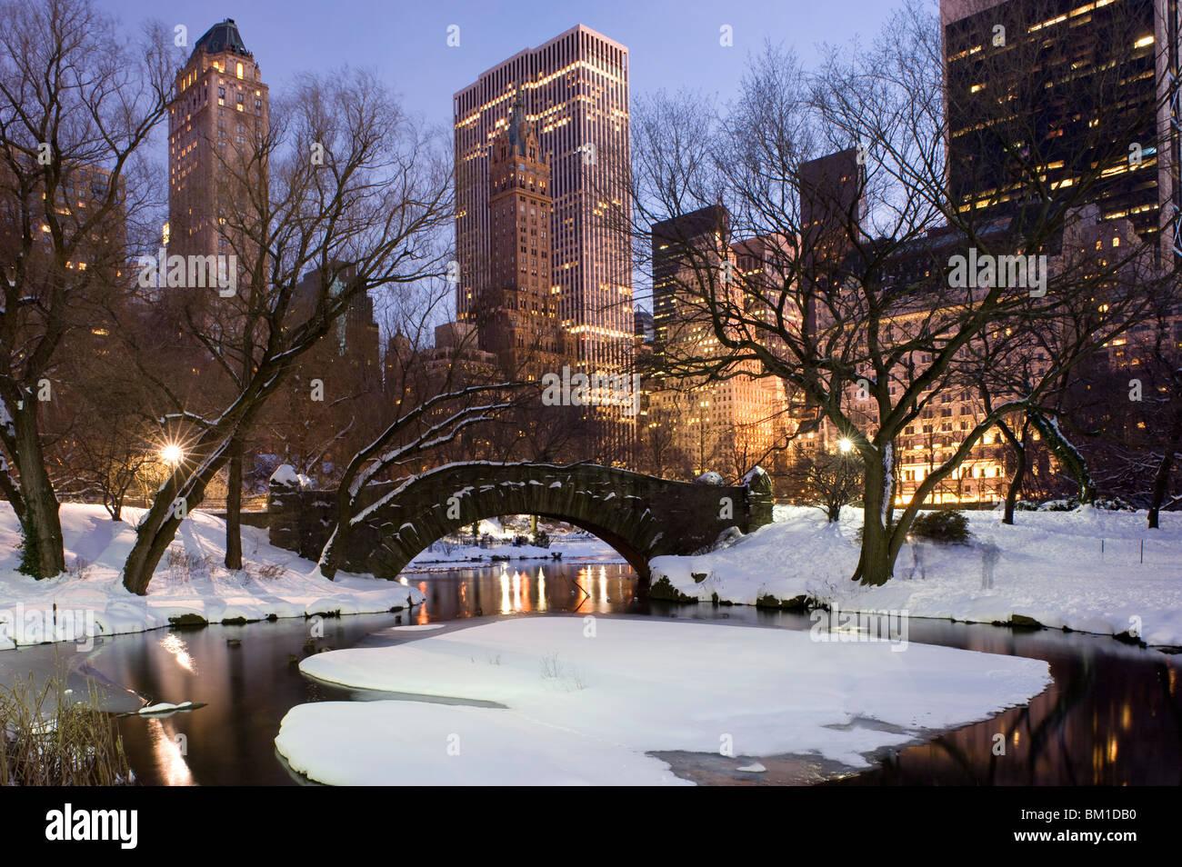 El Gapstow Bridge en Central Park después de una tormenta de nieve con rascacielos detrás al anochecer, la ciudad Foto de stock