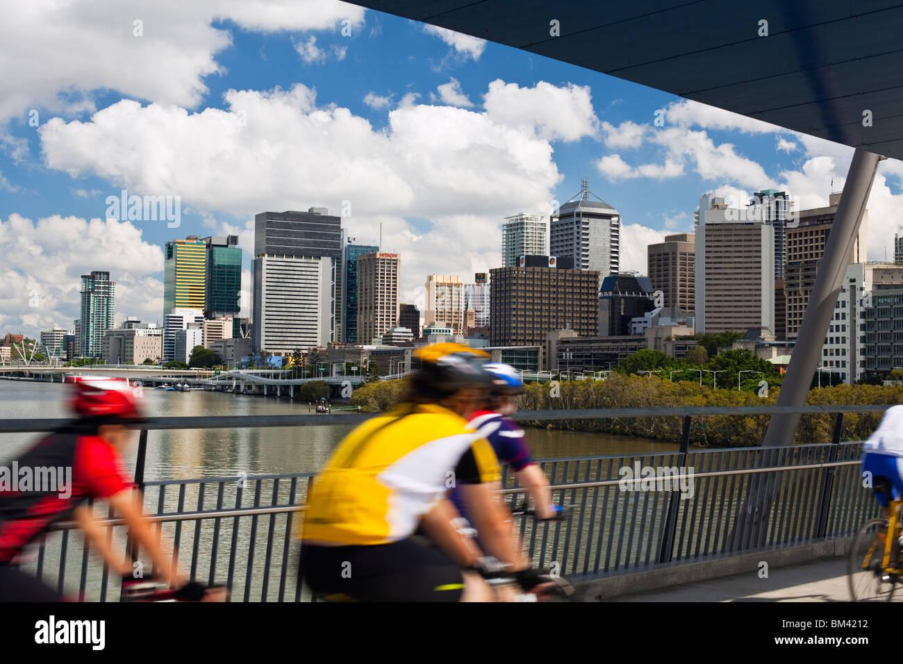 Los ciclistas en el puente de buena voluntad con el perfil de la ciudad de fondo. South Bank, Brisbane, Queensland, Imagen De Stock