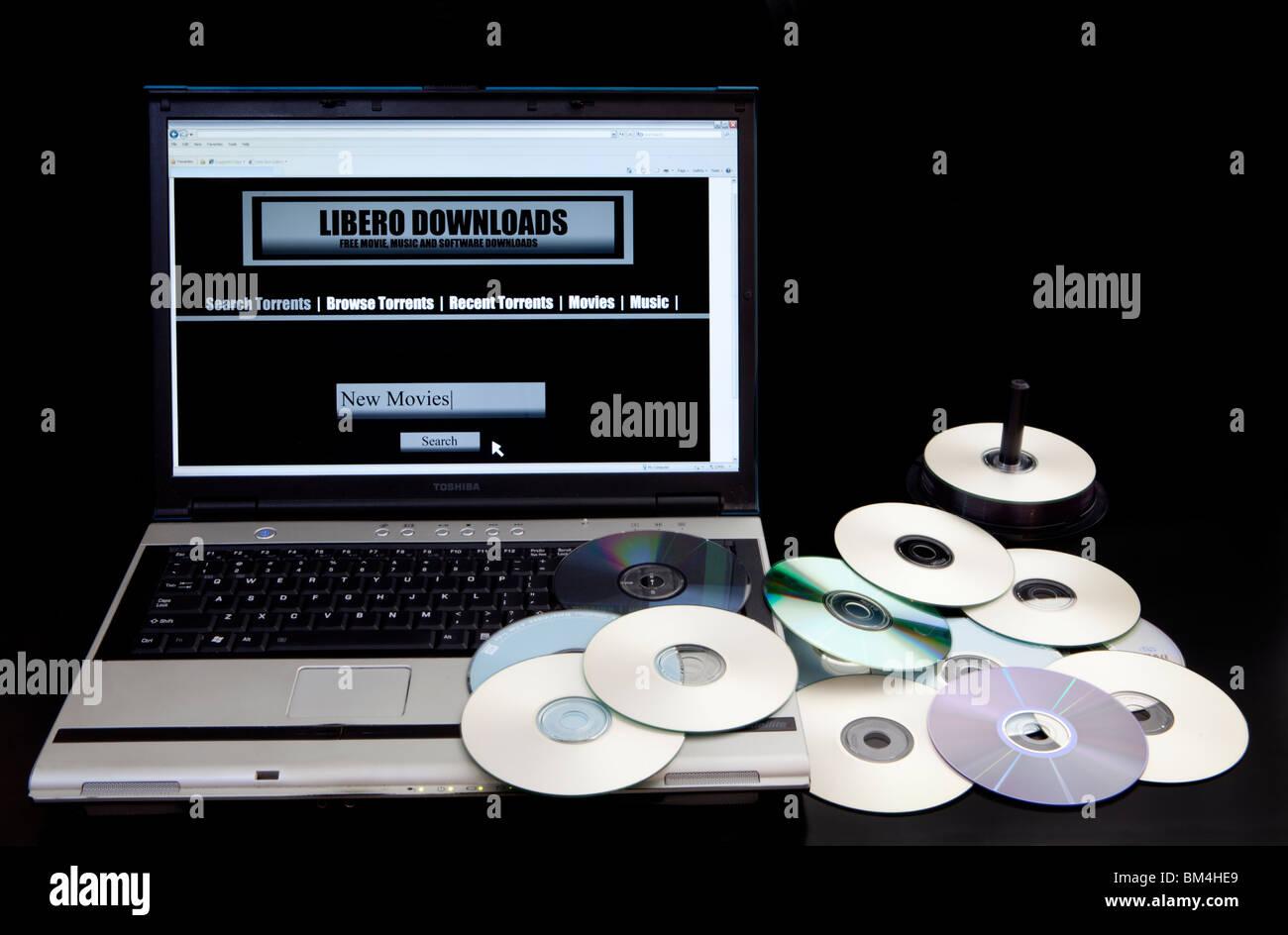 Sitio web de descarga ilegal y sitio de bittorrent en un equipo junto a un montón de copiado DVD. Imagen De Stock