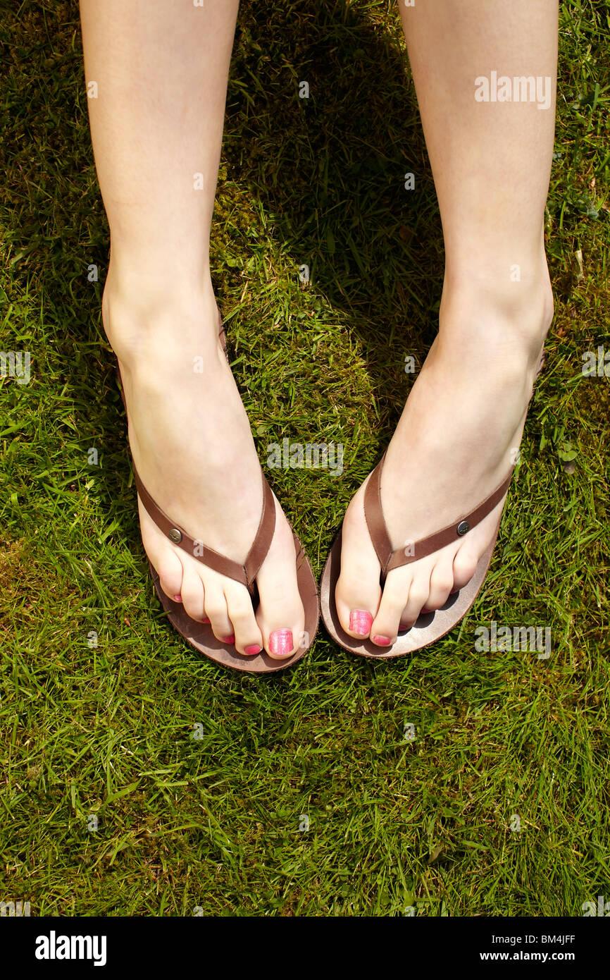 Cerca de pies en chanclas Foto de stock