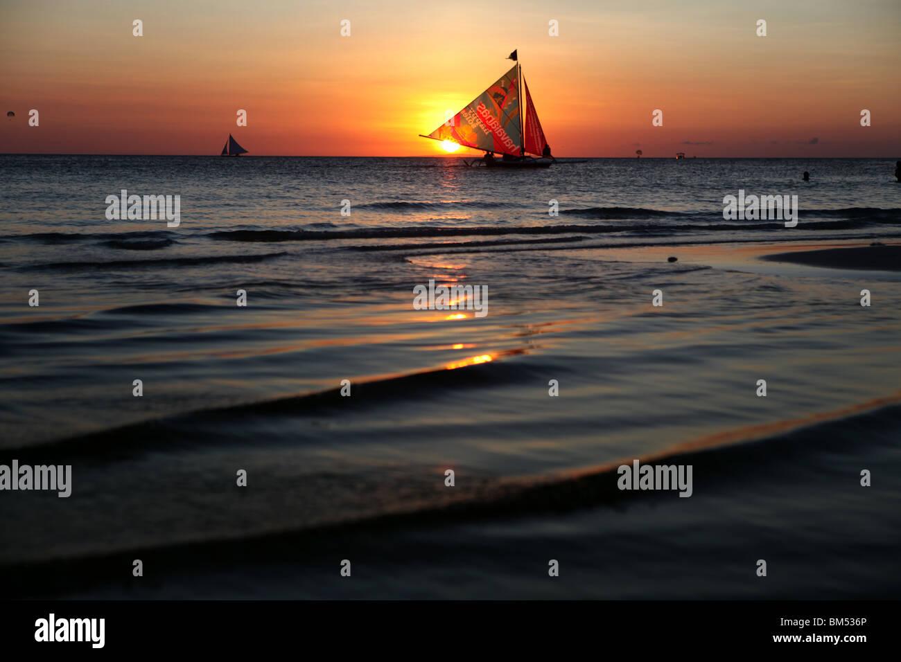 Un bote de vela pasa el atardecer en la Playa Blanca, Boracay, el destino turístico más famoso en Filipinas. Imagen De Stock