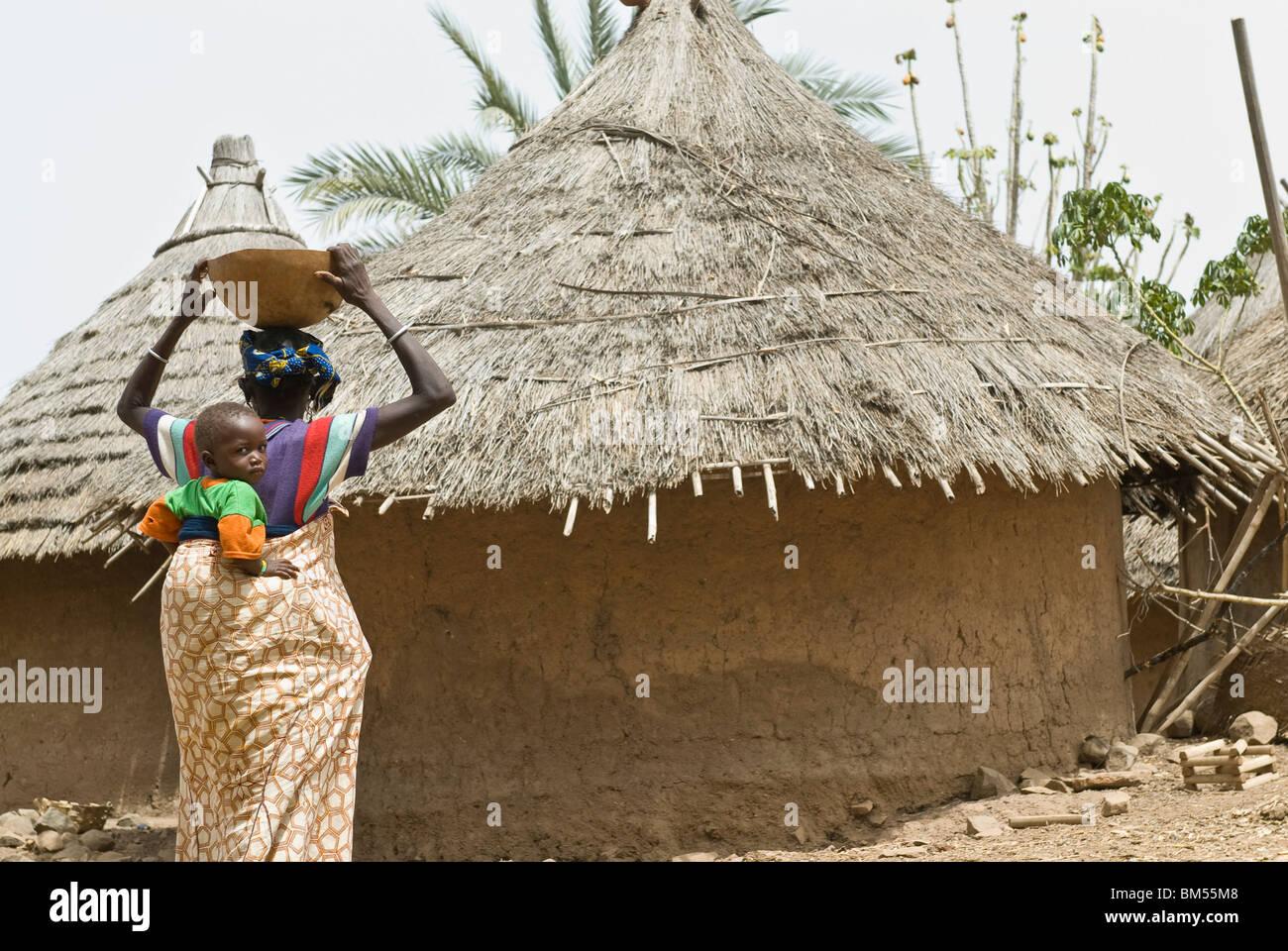 La mujer bedik africanos que llevan niños, Iwol village, país Bassari, Senegal, África. Imagen De Stock