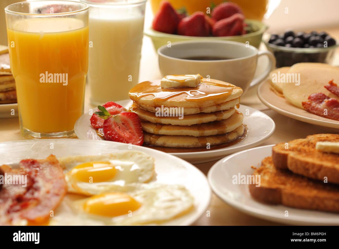 Desayuno tortitas, fruta, huevos, tocino y pan tostado Imagen De Stock