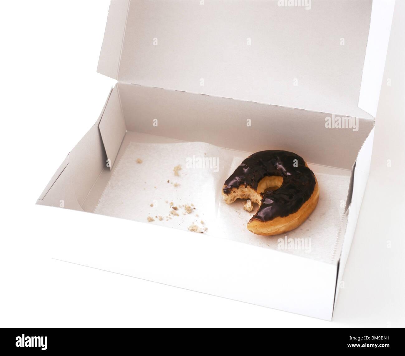Still life de una caja con una parcialmente comido donut Imagen De Stock