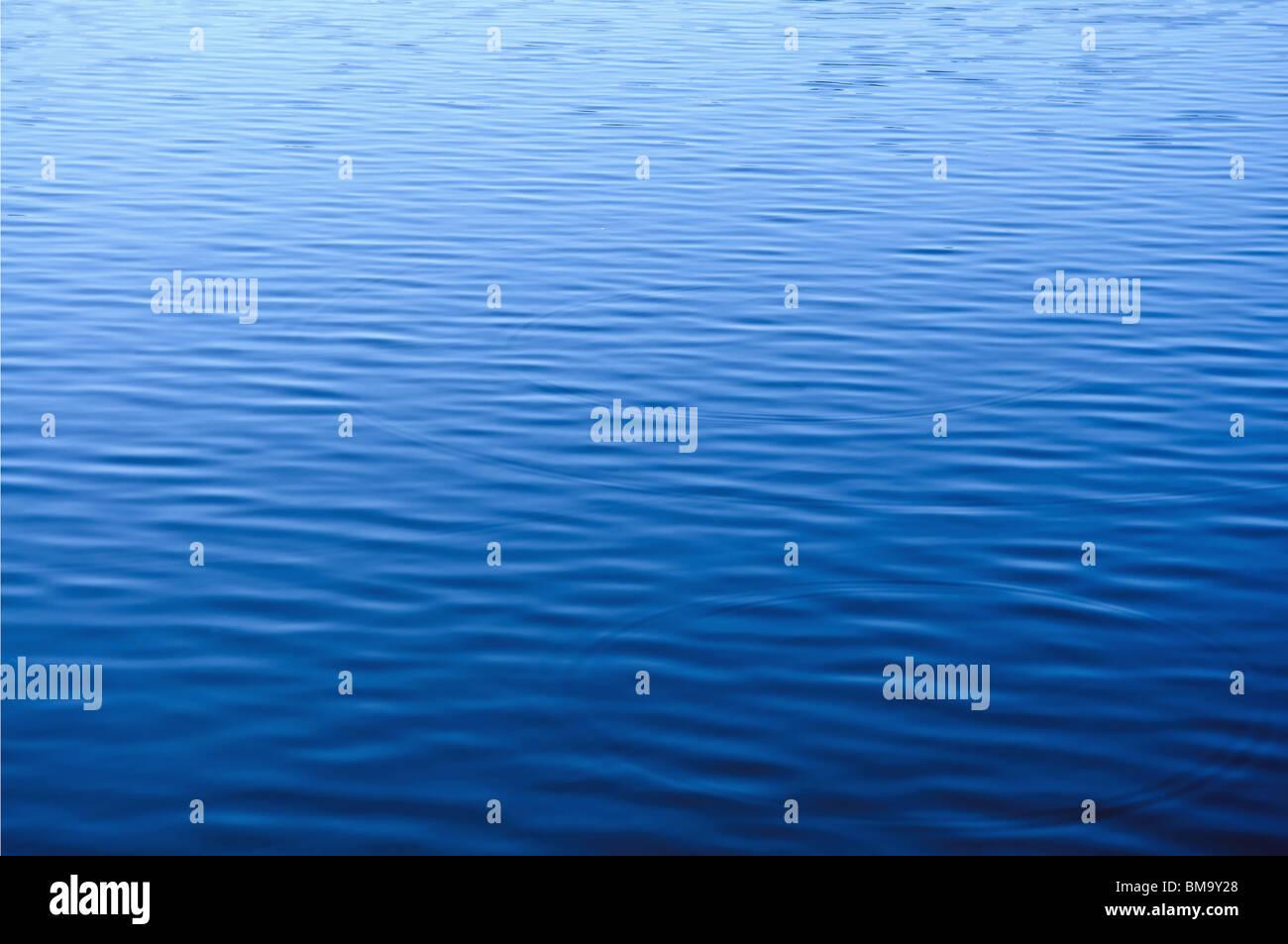 Superficie de agua azul con olas pequeñas Imagen De Stock