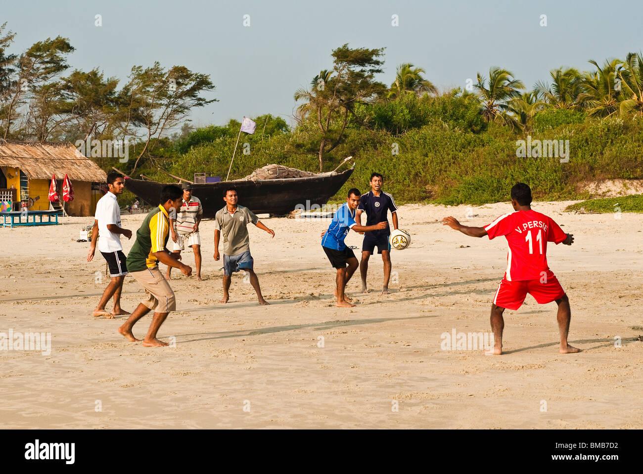La juventud local jugando al fútbol en la playa Varca, Goa, India Imagen De Stock