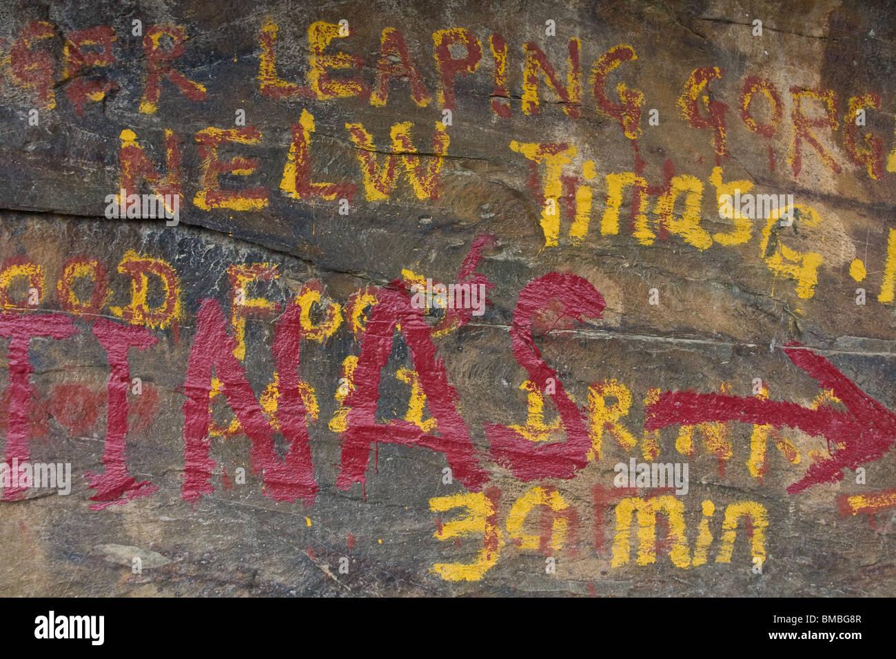 Escritura a mano sobre la roca de mostrar el camino a un backpacker's Guest House en TLG trek en Yunnan, China Imagen De Stock