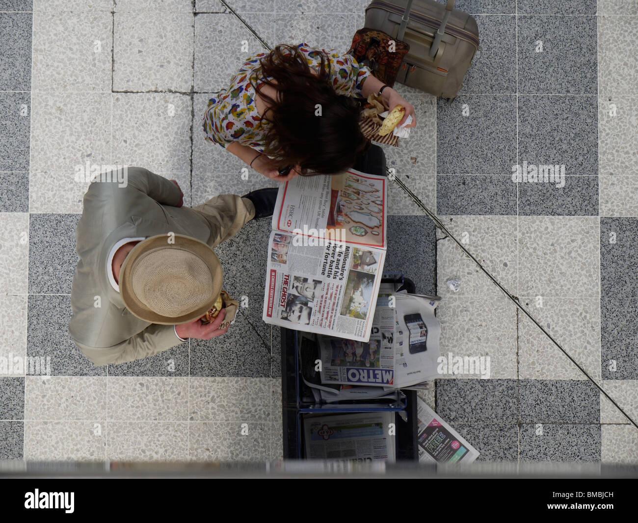 Los lectores del periódico gratuito metro en Liverpool Street Station de Londres Imagen De Stock