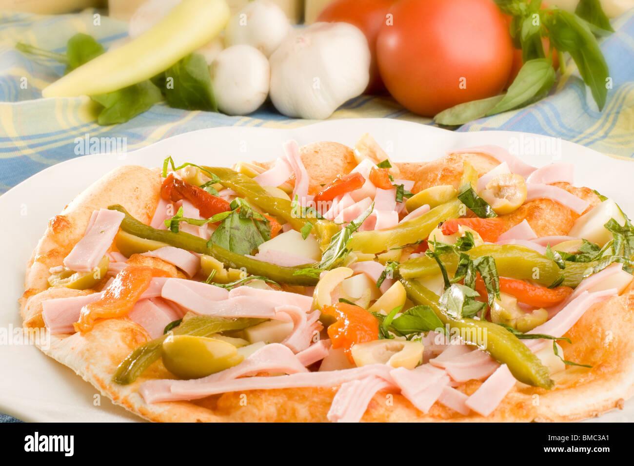 Pizza con jamón, aceitunas y Pimiento Capsicum Foto de stock
