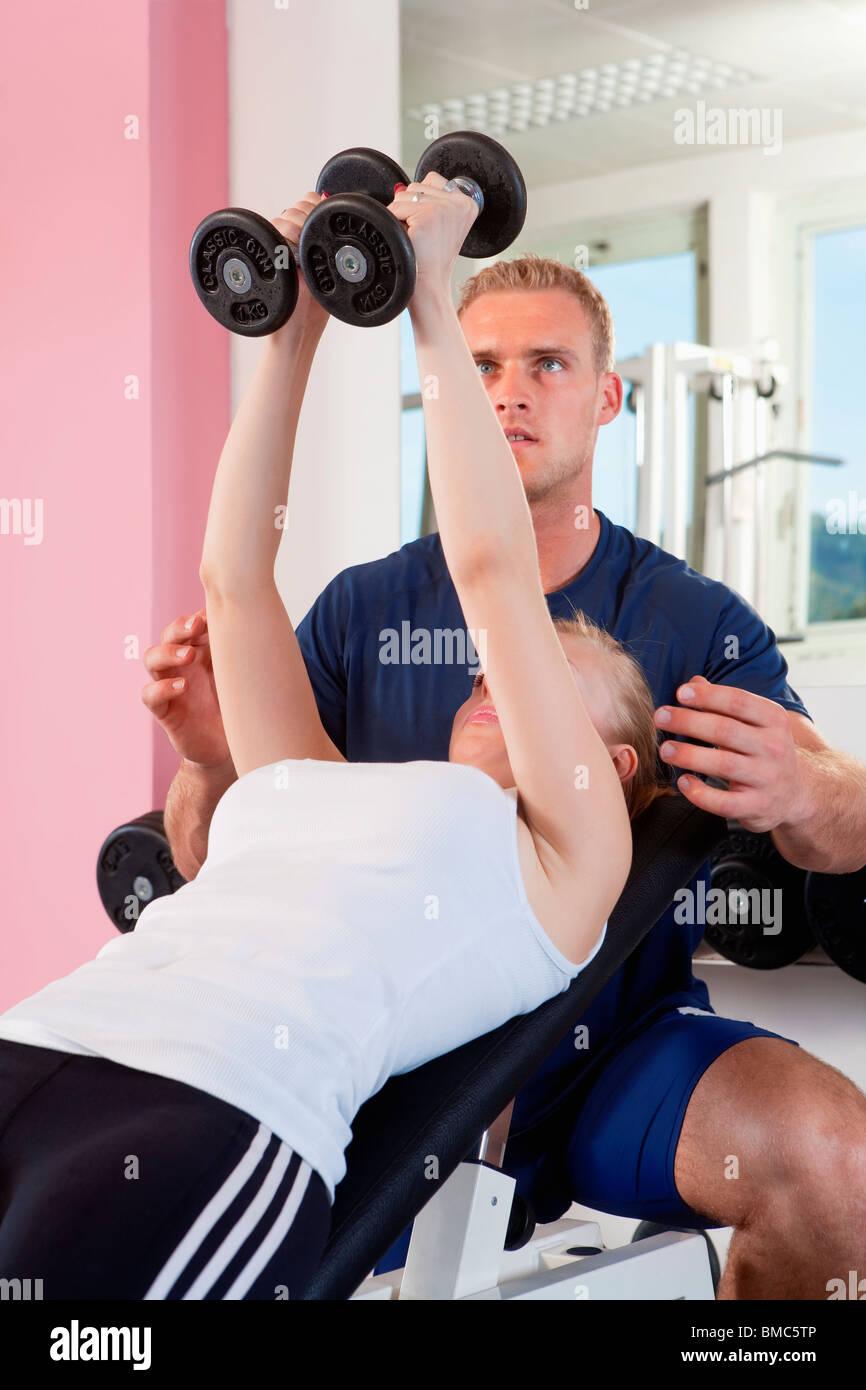 Joven de levantamiento de pesas en el moderno gimnasio con entrenador Foto de stock