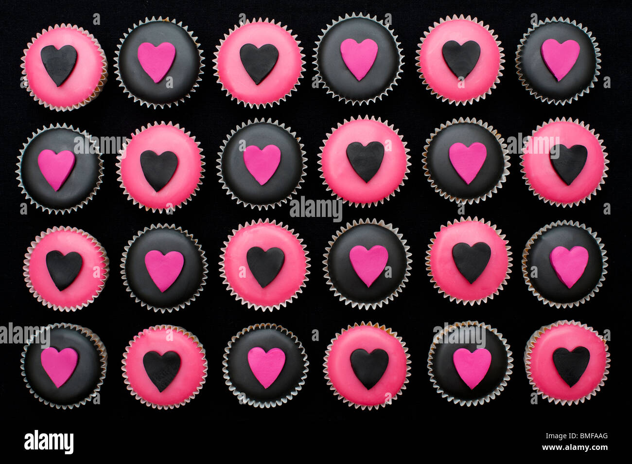 Mini magdalenas decoradas con glaseado rosa y negro y las formas del corazón Imagen De Stock