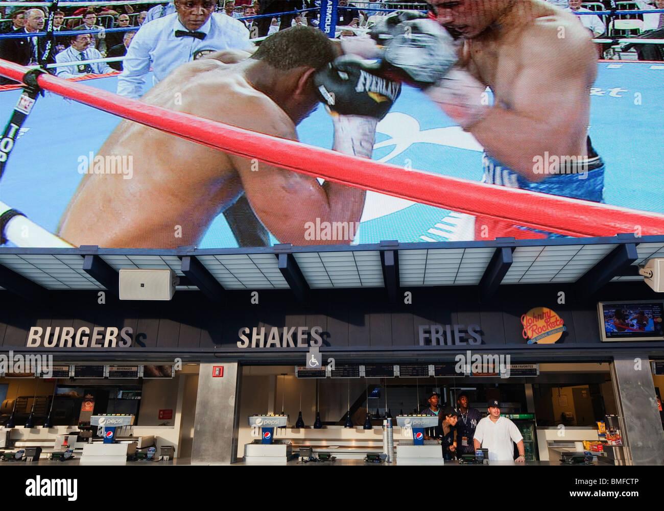 El Yankee Stadium kiosco los trabajadores mira a un combate de boxeo como la mega pantalla encima de ellas reproduce Imagen De Stock