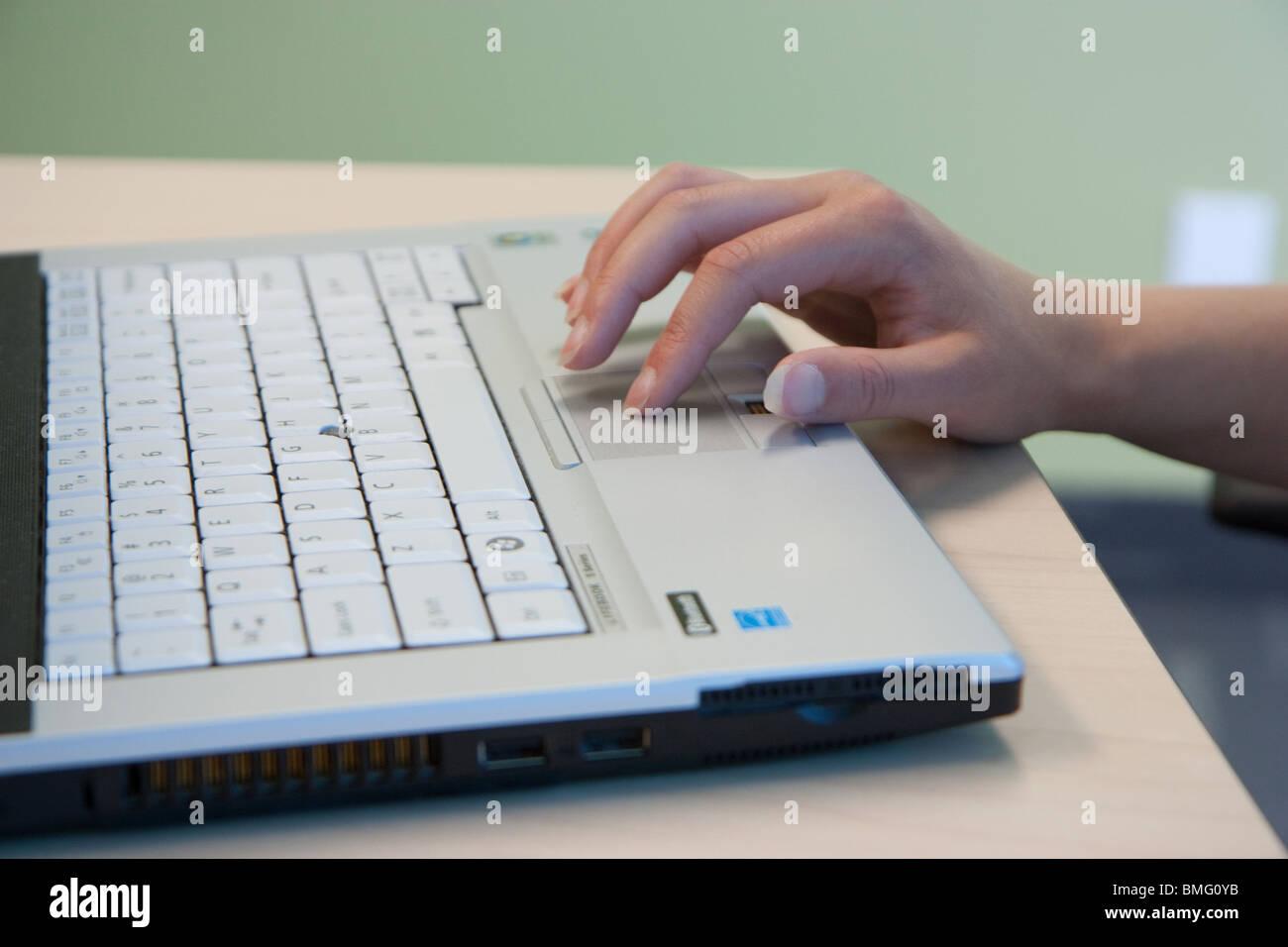 Los dedos femeninos closeup touchpad del portátil Imagen De Stock
