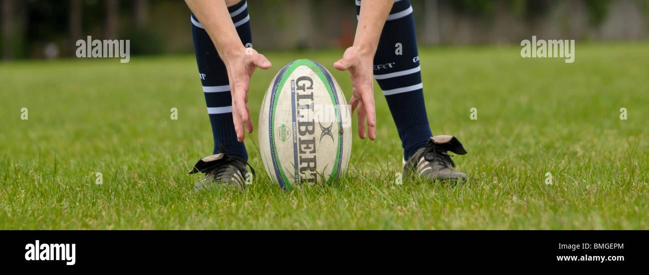 Jugador de rugby coloca una pelota de rugby Gilbert sobre el terreno preparado para un spot kick, dos manos a ambos Imagen De Stock