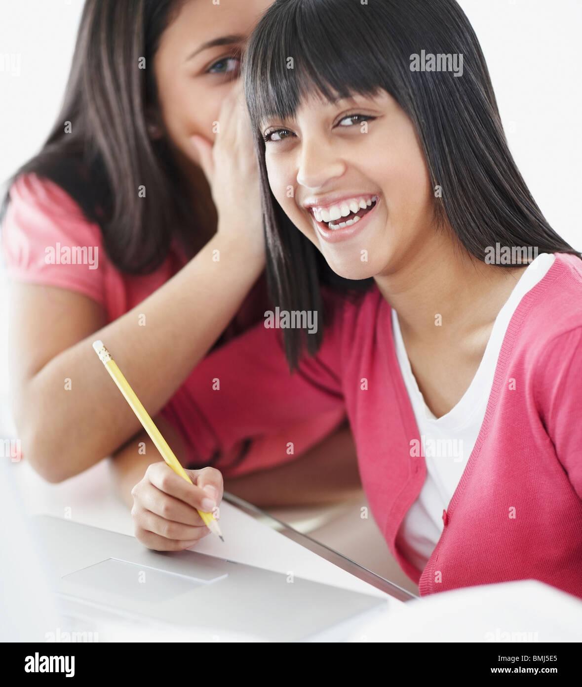 Los estudiantes susurrando en el aula Imagen De Stock