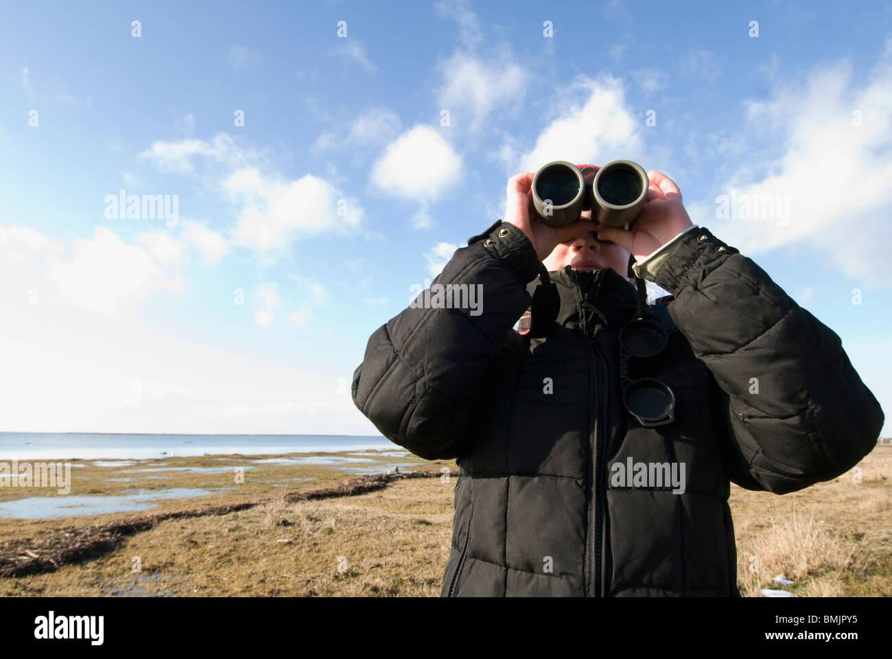Escandinavia, Suecia Öland, Chica (8-9) mirando a través de binoculares Imagen De Stock