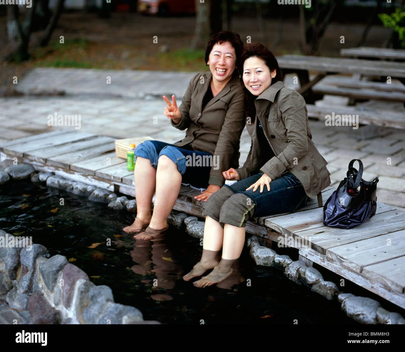 Las mujeres japonesas empapa los pies en aguas cálidas en un onsen en Beppu Imagen De Stock