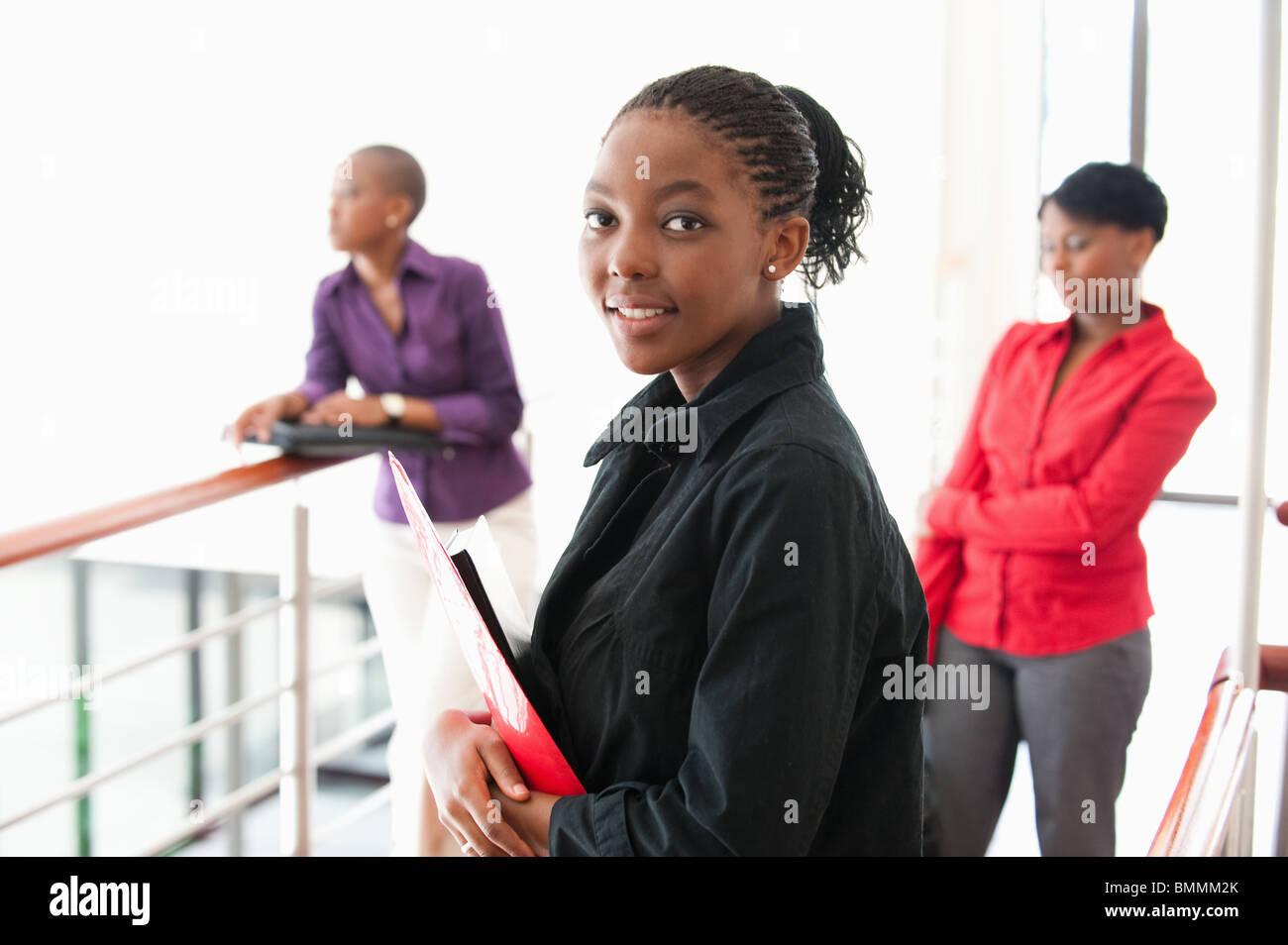 Retrato de joven empresaria con dos mujeres en el fondo, Johannesburgo, en la provincia de Gauteng, Sudáfrica Imagen De Stock