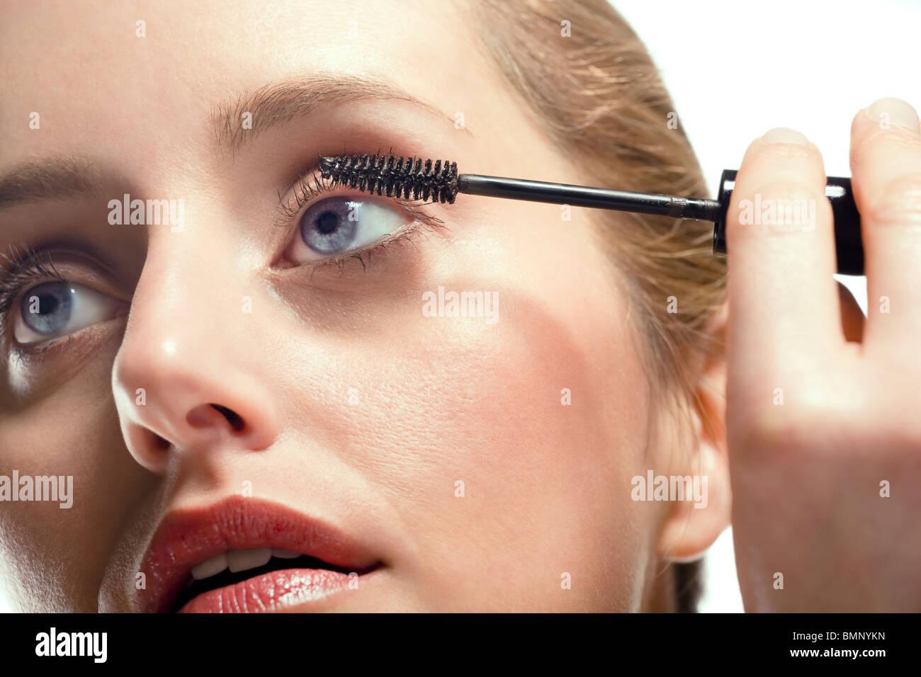 Close-up de mujer aplicar mascara sobre fondo blanco. Imagen De Stock