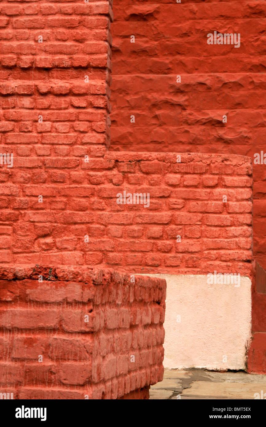 Resumen ; las paredes de ladrillo pintado de rojo y diversas formas cuadradas Foto de stock