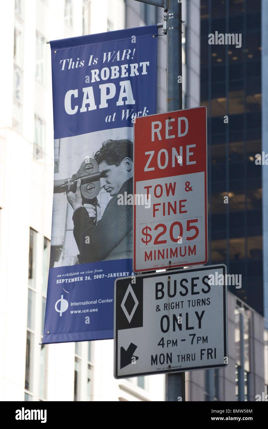 Zona roja y los autobuses sólo los letreros de la calle en Nueva York con Robert Capa Exposición Foto de stock