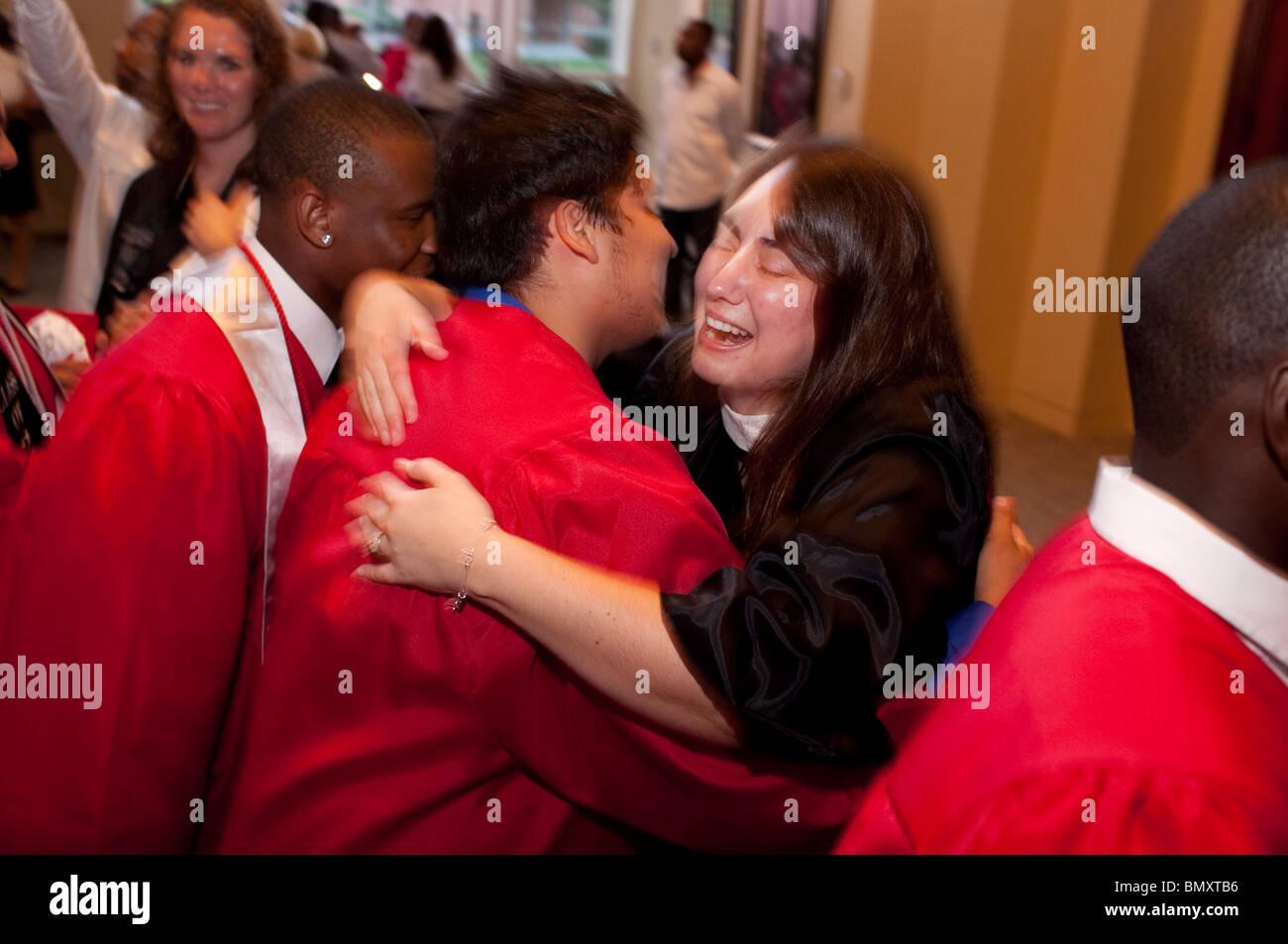 Niño hispano abrazos bien wisher después de la ceremonia de graduación de la Academia Kipp High School en Houston, Texas, EE.UU. Foto de stock