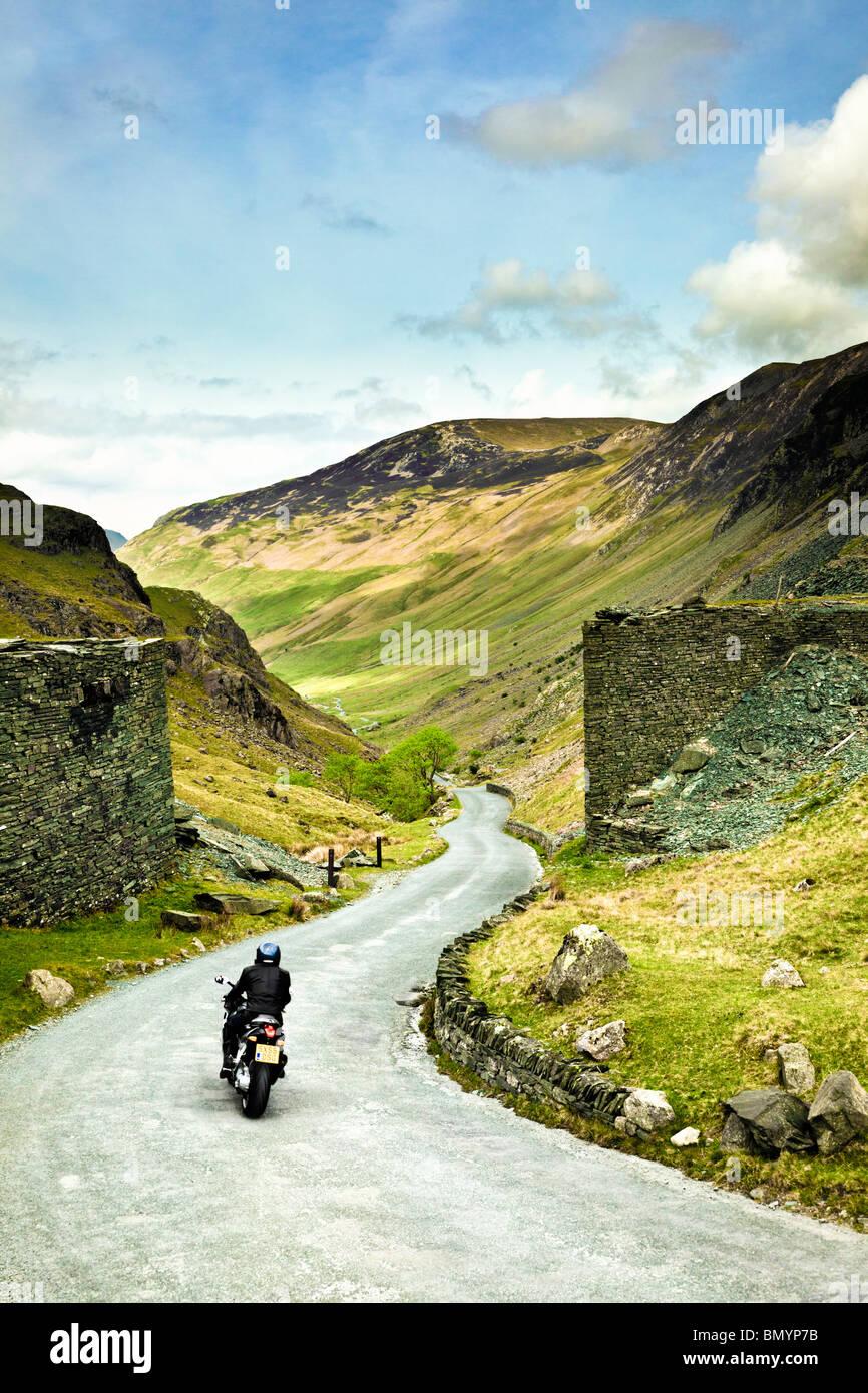 El motorista en viaje por carretera a través de una carretera de montaña en Honister Pass en el Lake District, Imagen De Stock