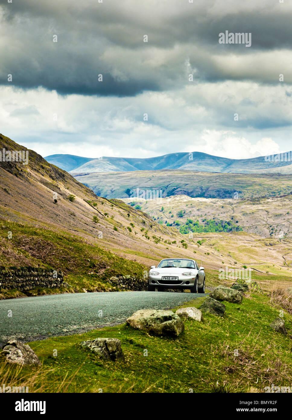 Conducción, UK, coche deportivo conducir en una carretera de montaña en el distrito de Los Lagos, en un Imagen De Stock