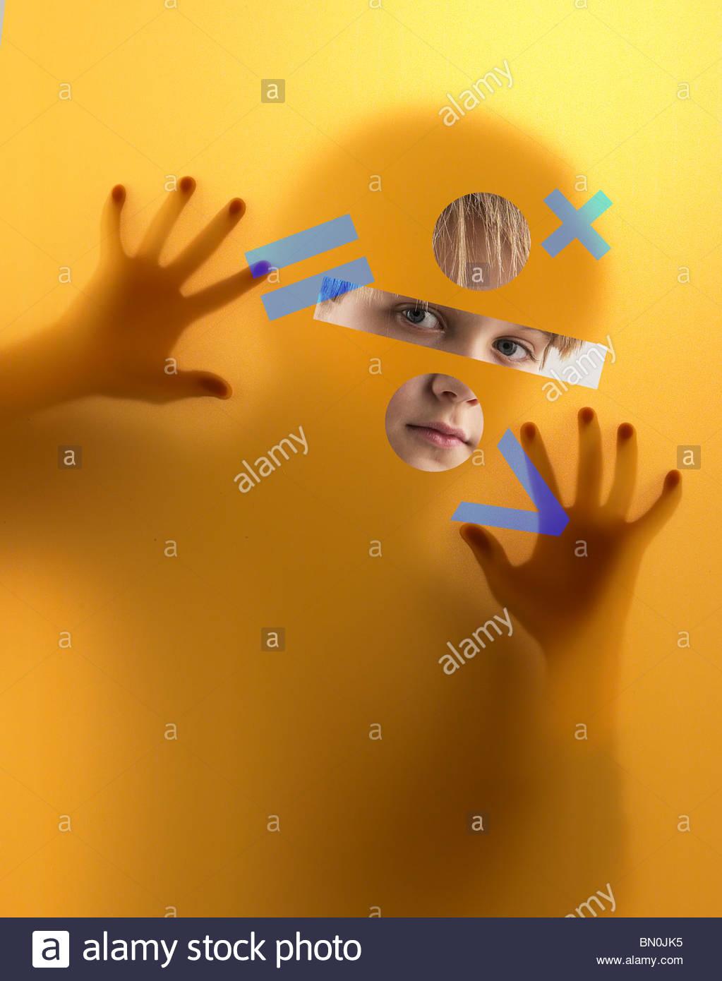 Un niño mira a través de una pantalla cubierta de símbolos matemáticos Foto de stock