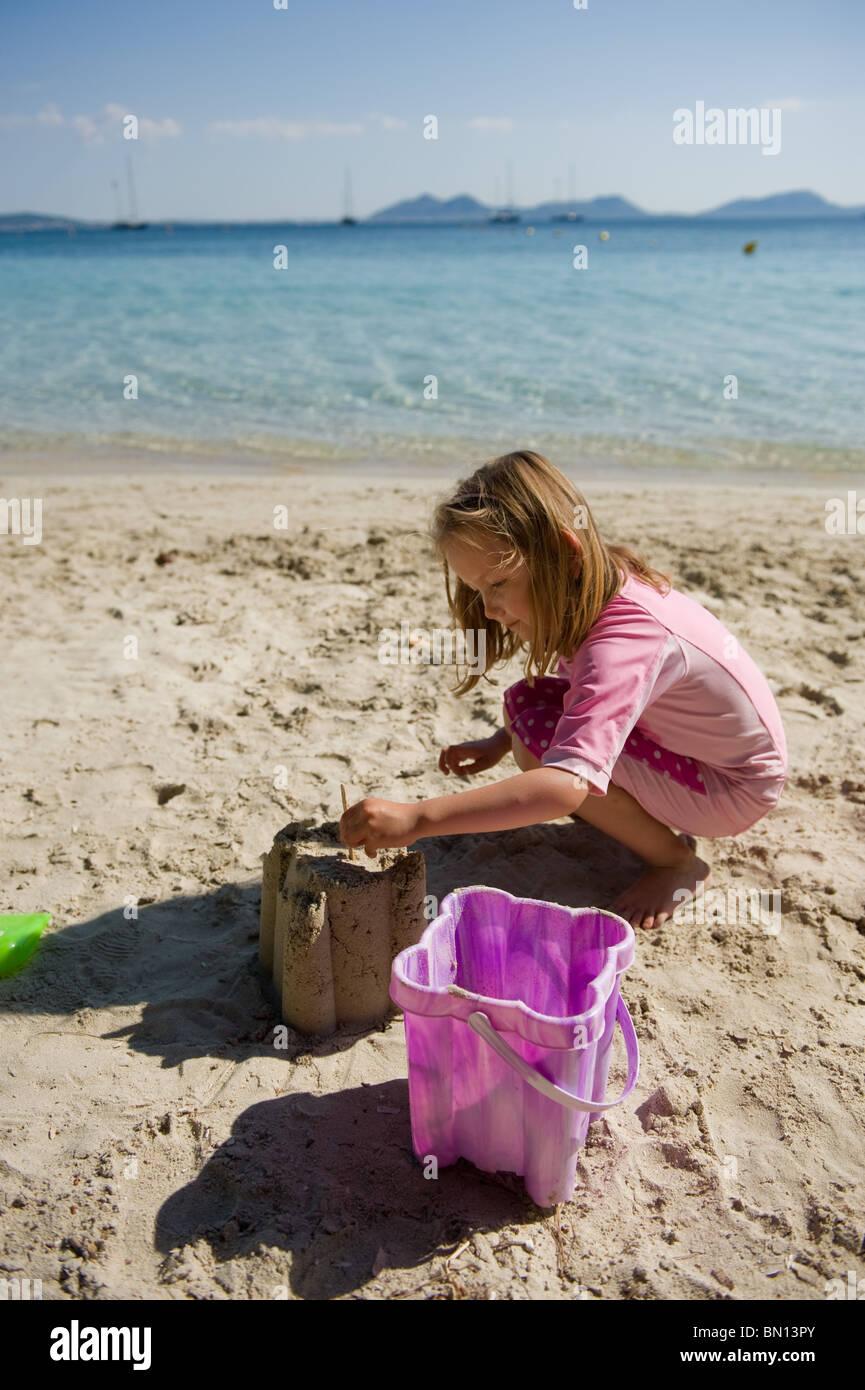 Una niña de cinco años haciendo un castillo de arena en la playa de Formentor en Mallorca, España 2010 Foto de stock