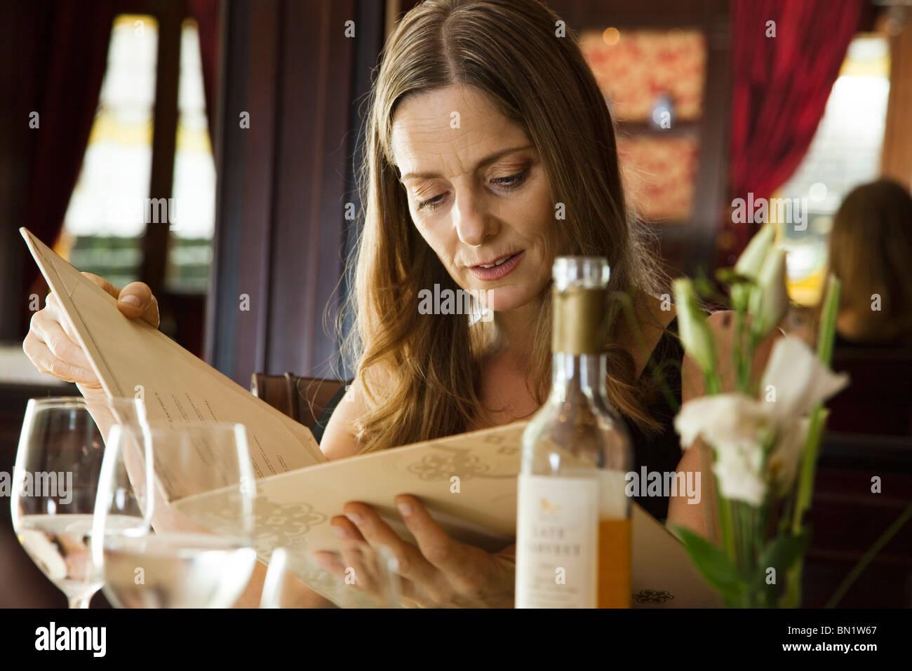 Mujer madura, busca en el menú en el restaurante Imagen De Stock