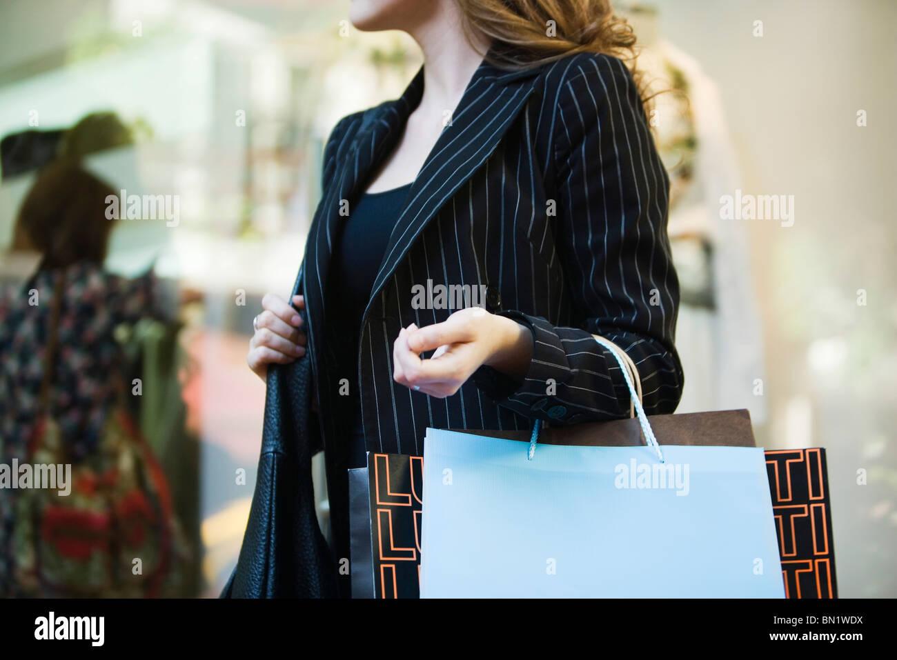 Mujer llevando bolsas de compras, recortadas Imagen De Stock