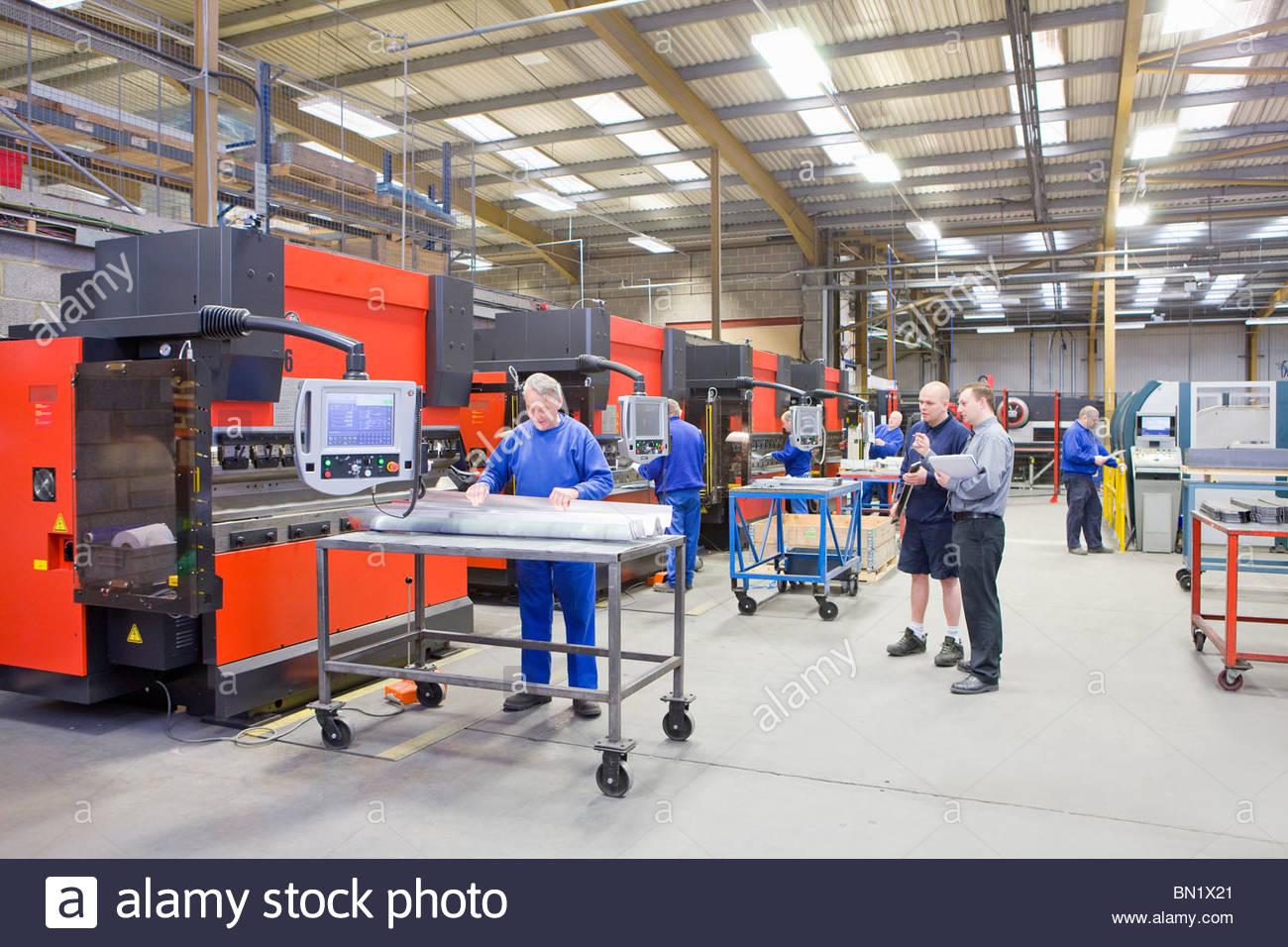Los trabajadores y las máquinas en la fábrica que fabrica accesorios de luz de aluminio Imagen De Stock