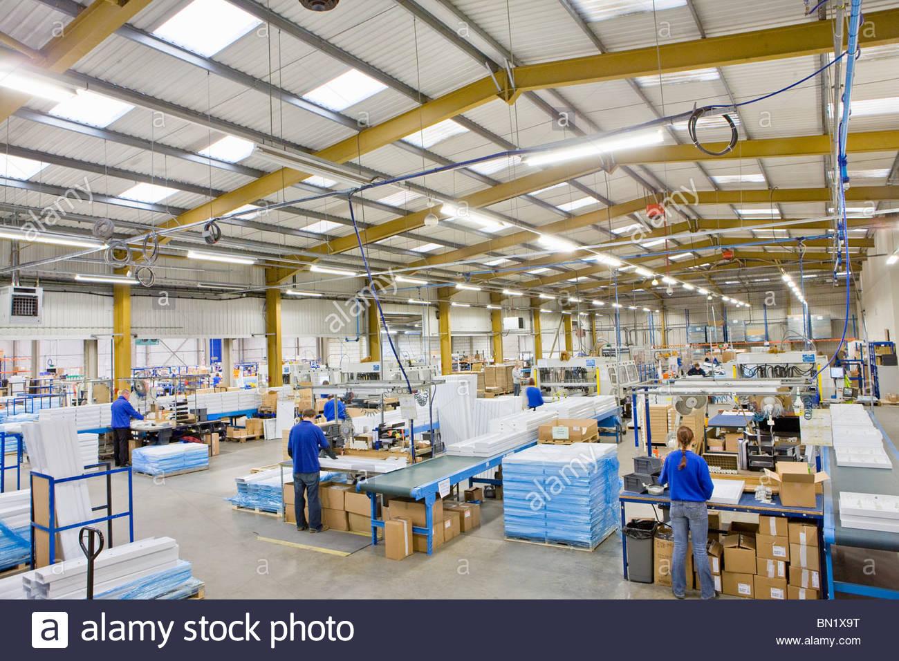 Los trabajadores de línea de producción en la fábrica que fabrica accesorios de luz de aluminio Imagen De Stock