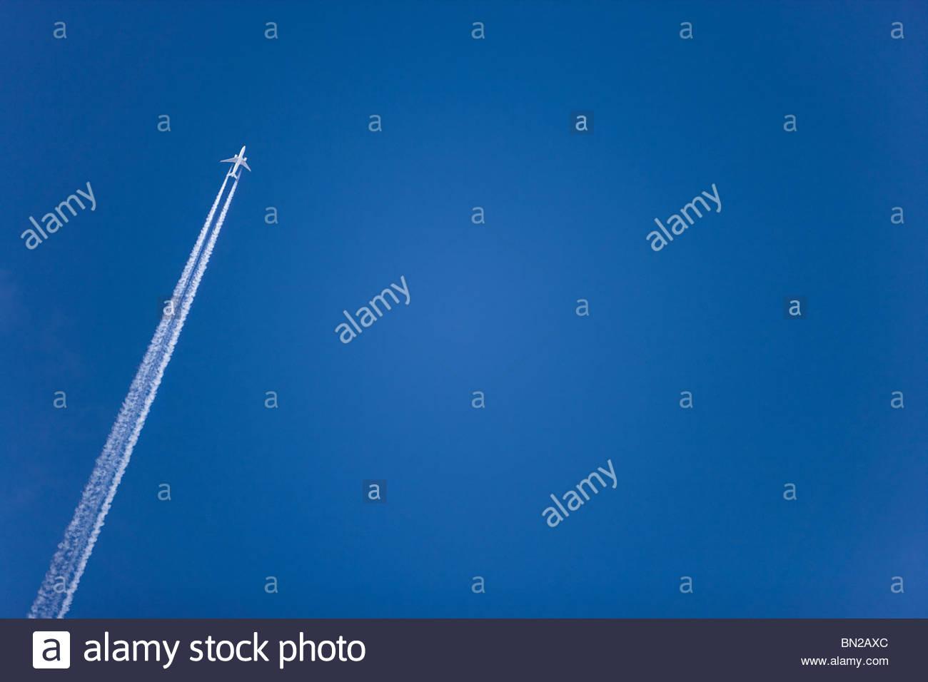 Avión con estelas de condensación volando en el cielo azul claro Imagen De Stock