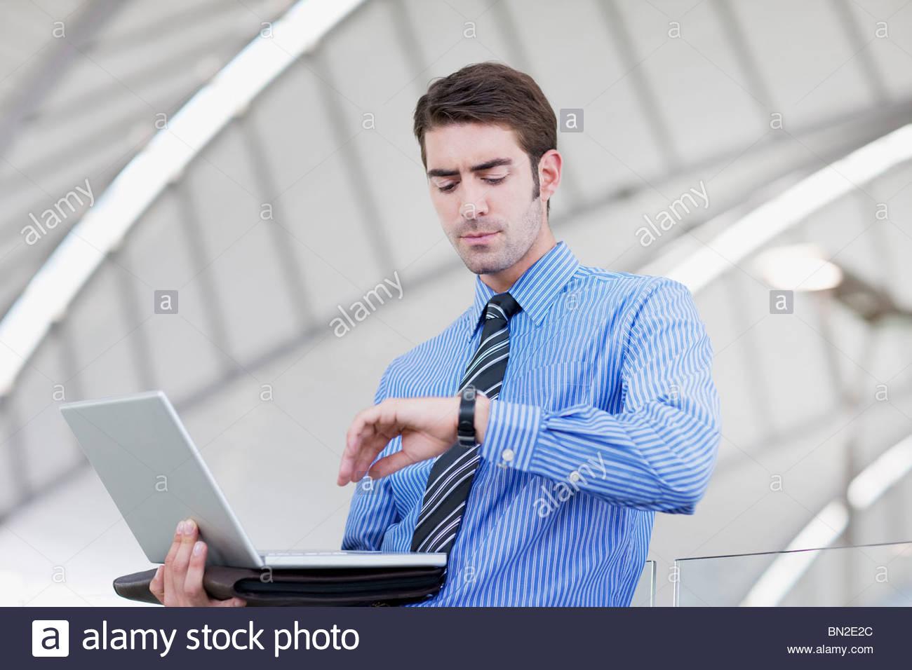 Empresario con laptop Comprobación del tiempo Imagen De Stock